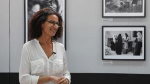 La photographe Nadia Benchallal devant ses photos rassemblées dans la série Sisters, Femmes musulmanes dans le monde