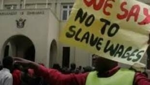 Zimbabwe state worker on strike displays poster in the capital Harare