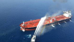 An Iranian navy boat tries to stop the fire of an oil tanker after it was attacked in the Gulf of Oman, June 13, 2019.