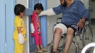 Syrian girls and their father at the Red Crescent Hospital in Amman, 3 July, 2012