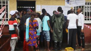 Les électeurs se rassemblent devant un bureau de vote inondé lors de l'élection présidentielle à Kinshasa, en République démocratique du Congo, le 30 décembre 2018.