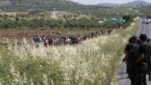 Policiais turcos (à dir.) observam sírios tentando atravessar a fronteira, fugindo da violência.