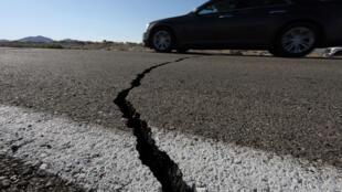 Um carro passa por cima de uma fissura que se abriu em uma estrada durante um terremoto que atingiu o sul da Califórnia, perto da cidade de Ridgecrest, Califórnia, EUA, 4 de julho de 2019.