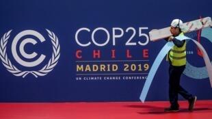 Travailleur passant devant le logo de la COP 25, au Palais des congrès de Madrid, le 30 novembre 2019.