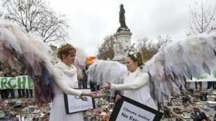 Deux manifestantes pacifiques place de la République à Paris.Tout rassemblement ayant été interdit par mesure de sécurité, les candidats à la manifestation avaient déposé des chaussures au sol.