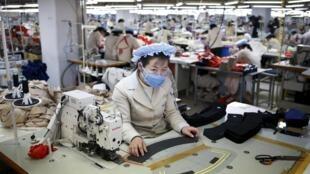 Công nhân Bắc Triều Tiên làm việc tại một xưởng may của Hàn Quốc trong khu công nghiệp Kaesong. Ảnh chụp ngày 19/12/2013.