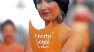 Militante pró-aborto protesta contra as condições impostas às mulheres que desejam interomper a gravidez em um projeto de lei aprovado nseta terça-feira pelos deputados uruguaios.