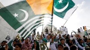 Người Pakistan phất cờ Pakistan (P) và cờ Cachemire (T) tỏ sự đoàn kết với dân Cachemire. Ảnh chụp tại Karachi, ngày 14/08/2019.