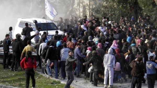 Les civils se rassemblent autour d'un véhicule des Nations unies en attendant d'être évacuées d'une zone assiégée de Homs, le 10 février 2014.