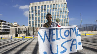 Un hombre despliega un afiche de bienvenida frente a la Embajada de Estados Unidos en La Habana.