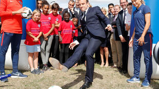 President Emmanuel Macron (C) visits a recreation centre