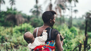 A woman carries her infant son on her back in Sierra Leone