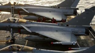 Aviões de combate Rafale se preparam para decolar do porta-aviões francês Charles-de-Gaulle, enviado ao mar Mediterrâneo.