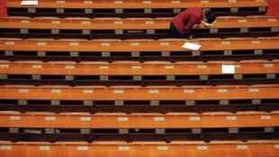An attendant searches delegates' desks after the closing 2016年3月14日,在中国北京人民大会堂举行的两会闭幕式结束后,与会人员在代表们的桌子上搜查。ceremony of the Chinese People's Political Consultative Conference (CPPCC) at the Great Hall of the People in Beijing, China, March 14, 2016.