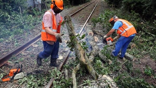 Railworkers clear branches from track near Pauillac, south-west France