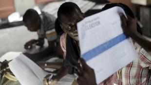 Un travailleur électoral examine le scrutin pendant le dépouillement dans un bureau de vote de Port-au-Prince, le 9 août 2015
