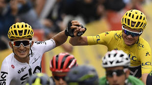 Great Britain's Christopher Froome (R), wearing the overall leader's yellow jersey, wins the Tour de France 2017 as he crosses the finish line with his teammate Poland's Michal Kwiatkowski on the Champs-Elysees.