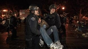 Riot police carry off an Occupy LA protester