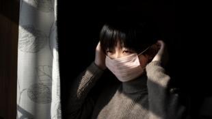 Lucy Huang, 26 ans, originaire de Wuhan et réalisatrice de documentaires vivant à Pékin, en train de mettre un masque de protection chez elle à Pékin, le 31 janvier 2020.
