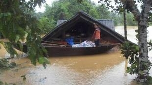 A girl stands on a boat near her submerged house in a flooded area of Vietnam's central Ha Tinh province