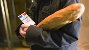 Proof of nationality - a voter brings his polling card and a baguette to the polling station