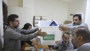 Autoridades de mesa preparan las urnas para las elecciones de este viernes en Amol, el 13 de junio de 2013.