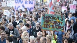 """A protestor holds a sign reading """"Macron president of rich people"""" during a protest over the government's labour reforms in Paris on September 23, 2017."""