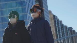 Des personnes portant des lunettes de neige et des masques dans le quartier central des affaires de Pékin, le 16 février 2020.