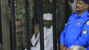 Le président soudanais déchu Omar el-Béchir dans le box des accusés lors de l'ouverture de son procès pour corruption à Khartoum, le 19 août 2019.