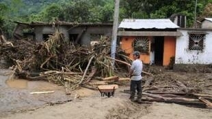 A man stands near debris washed up by flood waters in Villahermosa