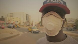 Un Dakarois porte un masque pour se protéger de la poussière, mardi 25 février, à cause de la tempête de poussière.