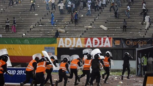 Police officers run with shields as Senegalese football fans throw rocks at them at Leopold Sedar Senghor stadium in Dakar