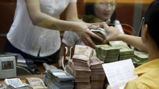 Khách hàng nộp tiền mặt tại một ngân hàng ở Hà Nội.