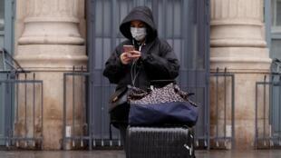 Les opérateurs télécoms appellent à privilégier les réseaux wifi, au lieu des mobiles. Ici, une femme près de la Gare du Nord à Paris, après le début du confinement en France, le 17 mars 2020.