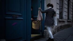 Un membre de l'association AMAP (Association pour le maintien d'une agriculture paysanne) rapporte un panier de légumes à une personne confinée dans son appartement à Paris, le 18 mars 2020.