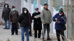 Des personnes font la queue devant une pharmacie équipés de masque à Sofia en Bulgarie, le 22 mars 2020;