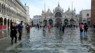 អ្នកទេសចរដើរលុយទឹក នៅទីលានខាងមុខព្រះវិហារ San Marco ទីក្រុងវ៉េនីស ថ្ងៃទី១៦ វិច្ឆិកា ២០១៩