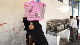 A Palestinian woman carries bottles filled with water from a public tap in Khan Younis in the southern Gaza Strip