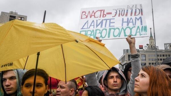 """Manifestante con una pancarta que lee """"El poder, somos nosotros. ¡Dennos el derecho de voto!"""" durante una marcha en Moscú, el 10 de agosto de 2019, tras detenciones masivas por la policía."""