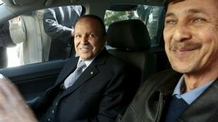 Algeria's President Abdelaziz Bouteflika smiles as he arrives with his brother Said at his campaign's communications department during a surprise visit in Algiers, Algeria April 10, 2009.