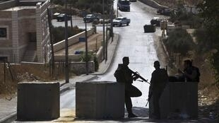 Israeli paramilitary border police stand guard at a roadblock in East Jerusalem