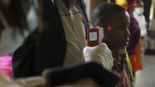 Funcionários do aeroporto internacional de Abuja, na Nigéria, medem a temperatura dos passageiros que chegam de países afetados pelo Ebola.