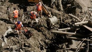 Rescuers use sniffer dogs to search for survivors under the rubble after flash floods in the town of Leh, in Ladakh province.