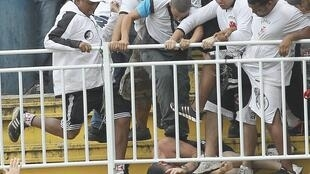 Torcedores do Vasco da Gama agridem violentamente torcedor do Atlético Paranaense no jogo valendo pelo Campeonato Brasileiro em Joinville, Santa Catarina, em 8 de dezembro de 2013.