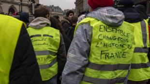 """""""با هم تاریخ فرانسه را تغییر دهیم"""" : شعاری یکی از تظاهرکنندگان پاریسی بر جلیقۀ خود نوشته است"""
