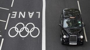 A taxi drives beside an Olympic traffic lane in Westminster, London