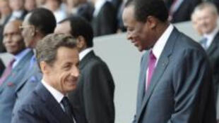 France's President Nicolas Sarkozy (L) shakes hands with Burkina Faso President Blaise Compaoré during the annual Bastille Day m