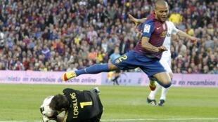 O jogador Daniel Alves, do Barcelona, desafia o goleiro do Real Madrid em clássico do dia 21 de abril, em Barcelona.