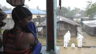 Médicos na capital liberiana Monróvia usam roupa protetora contra Ebola