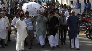 People carry the coffin of Sabeen Mahmud, a human rights activist killed by gunmen, during her funeral in Karachi, Pakistan, 25 April 2015